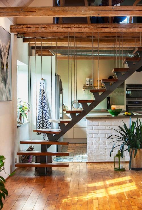 Trappan är specialbeställd av en smed och leder upp till parets kontor och ett extra sovrum. Den delar även av mellan köksdelen och matsalsdelen. Hunden Olle har koll på snabbaste vägen till matskålen.