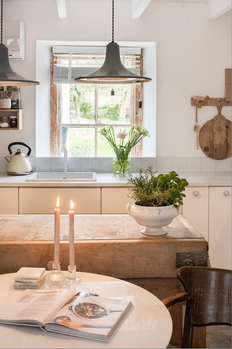 Fönsterbågarna i köket har lämnats omålade. Matbord och slaktarbänk kommer båda från Ebay. Underläggen i marmor har Linda gjort själv. Antik stol från Vadstena antik. Köket från Ikea har knoppar i marmor från Superfront.