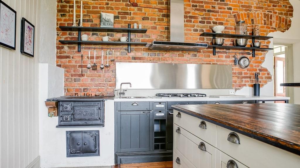 I köket finns en vacker tegelvägg ovan en del av arbetsytorna med ett rostfritt stänkskydd.
