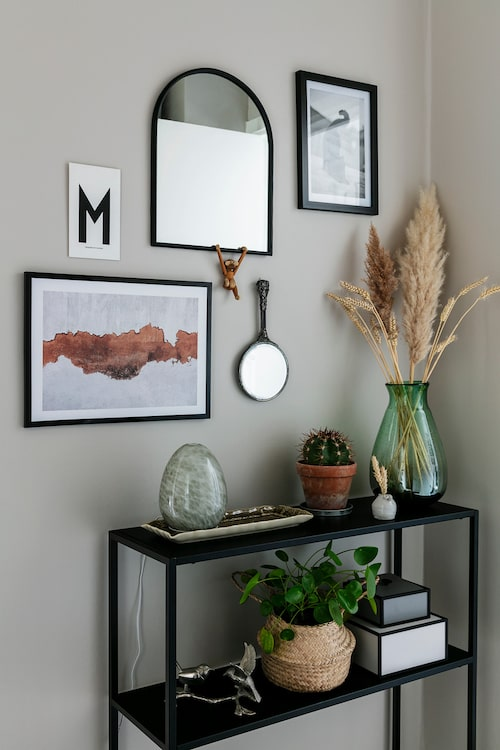 Hallen är rymlig med plats för vackra blickfång. Bord, Jysk, på väggen hänger prints från Desenio. Bokstavskort, Arne Jacobsen, apa i trä, Kay Bojesen, stor spegel, Mio. Den lilla handspegeln har Myriam ärvt av sin mormor. Glasägget är en doftspridare – Aroma Diffuser – från Sthlm Fragrance Supplier. Den stora vasen är ett loppisfynd, den lilla har Myriam gjort själv på en keramikkurs. Korg, Ikea, askar, ByLassen, fåglarna i silver är köpta på marknaden på Portobello Road i London.