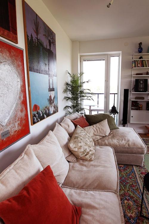 Rummet är inrett med härligt färgstarka målningar. Den generösa sandfärgade soffan har korallfärgade kuddar som matchar en hjärt-målning och den äkta mattan.