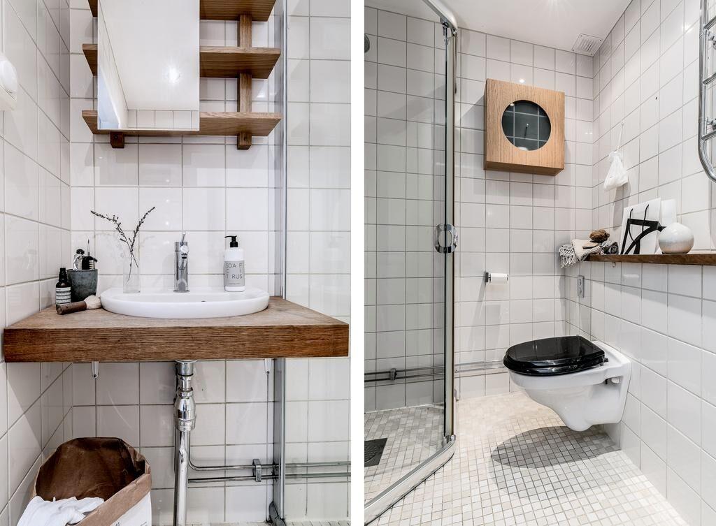Fräscht badrum med vita kaklade väggar och klinkergolv. Vägghängd WC och trendigt handfat som vilar på träskiva. Duschhörna med glasdörr.