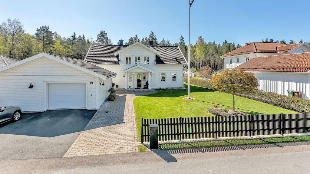 Framsidan av villan erbjuder fina stenläggningar, flaggstång och staket mot gatan.