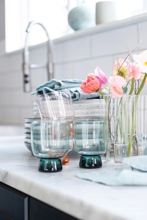 Vårljuset glittrar extra bra i glas. Glas, Åhléns. Linneservetter, Himla. Tallrikar och assietter, Denby. Köksblandare, Ikea.