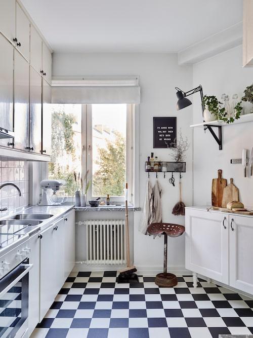 När Linnea och Carsten flyttade in gillade inte Linnea det rutiga golvet. Men nu när hon har inrett köket så att golvet och inredningen smälter samman har hon ändrat uppfattning. Gammal traktorpall från Blocket.