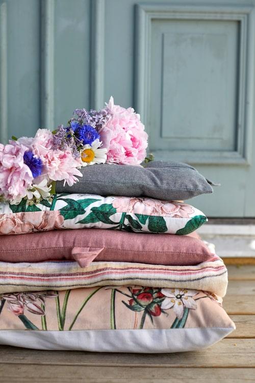 Blommig mönstrad kudde, 499 kronor, Oscar & Clothilde. Randig duk, 1 200 kronor, Soulosofie. Rosa sittkudde, 79 kronor, Hemtex. Blommig kudde, 99 kronor, H&M home. Grön sittkudde 79 kronor, Hemtex.
