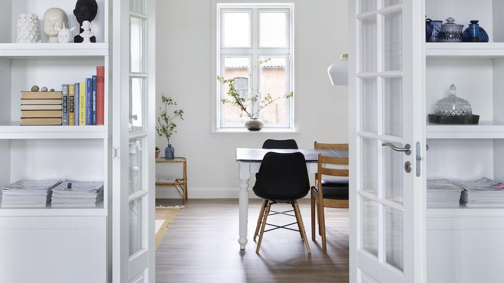 På väggen har paret platsbyggt en hylla som rymmer allt från prydnadssaker till böcker. Ovanför de franska pardörrarna hänger en målning som Tina fyndat på loppis.