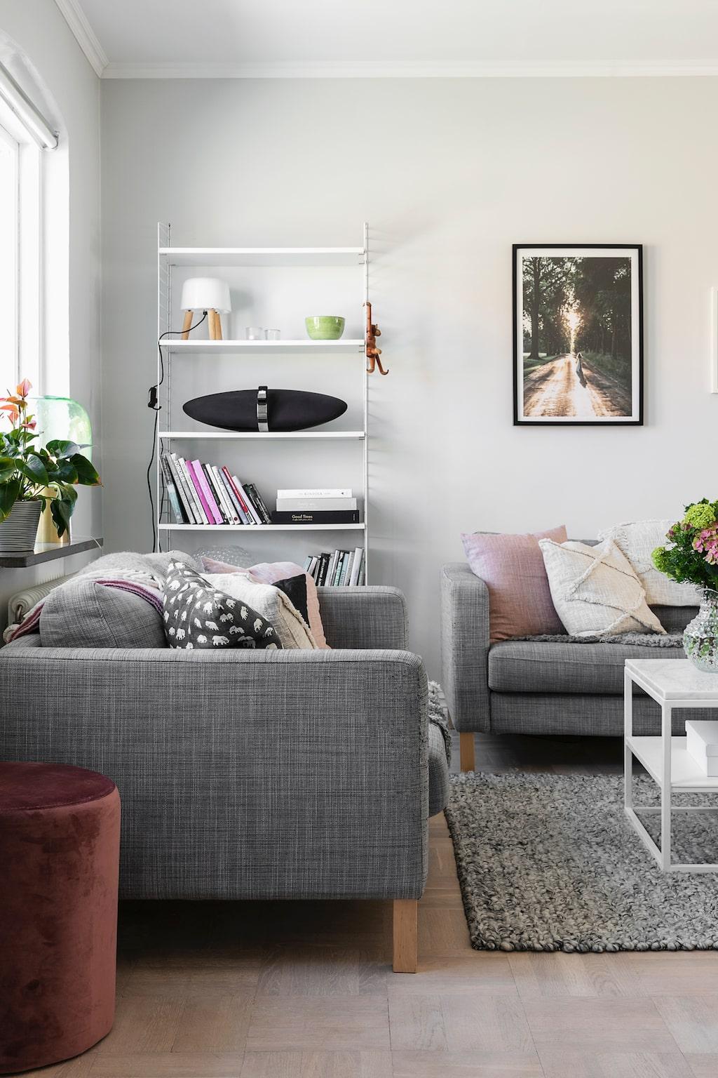 Vardagsrummet är omsorgsfullt inrett för att erbjuda lugn och harmoni. Cecilias favoritfärg rosa accepteras av Magnus så länge den ingår i en ljus och luftig helhet. Sofforna kommer från Ikea. Soffbordet är ett hemmabygge. Matta från Trendrum. Blandade kuddar från Svenskt Tenn, H&M Home och Dixie. I Stringhyllan står en lampa som sprider ett milt ljus genom sin mjölkvita skärm. Lampa från &tradition.