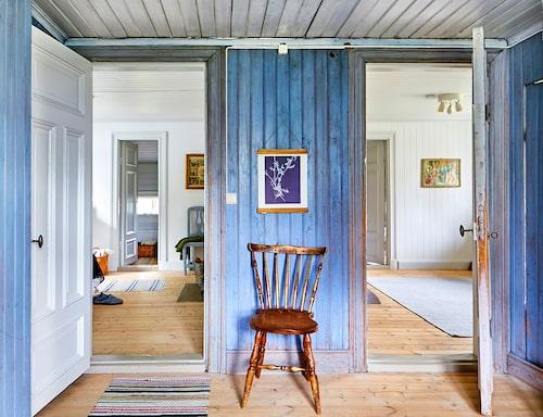 Den blå hallen fick styra färg och tapetval i resten av huset. Härifrån leder dörrar till sovrum och pysselrum. Skurgolven plockades fram under slitna plastgolv. De vackra trasmattorna låg i huset när familjen tog över. Stolen är köpt på bondauktion.
