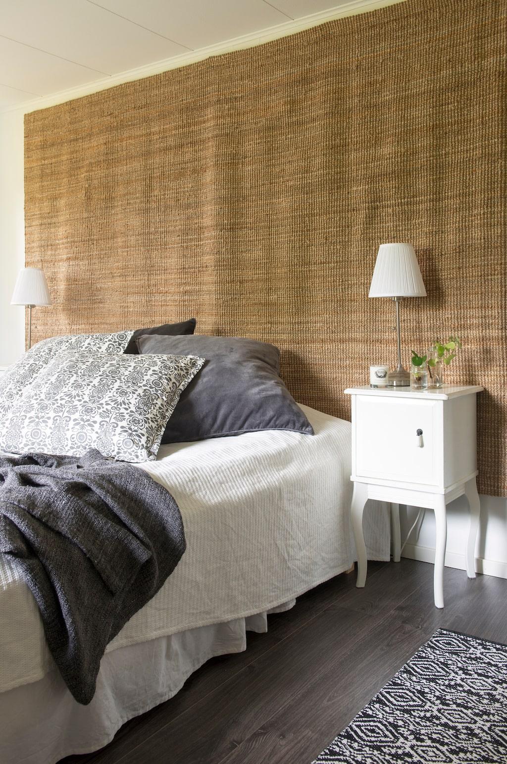 Alternativ gavel. I stället för sänggavel har Vanessa klätt väggen med en stor jutematta från Ikea. På sängbordet står två sticklingar av pilea och murgröna och ett doftljus från Klinta. Sängbord och lampor från Ikea.