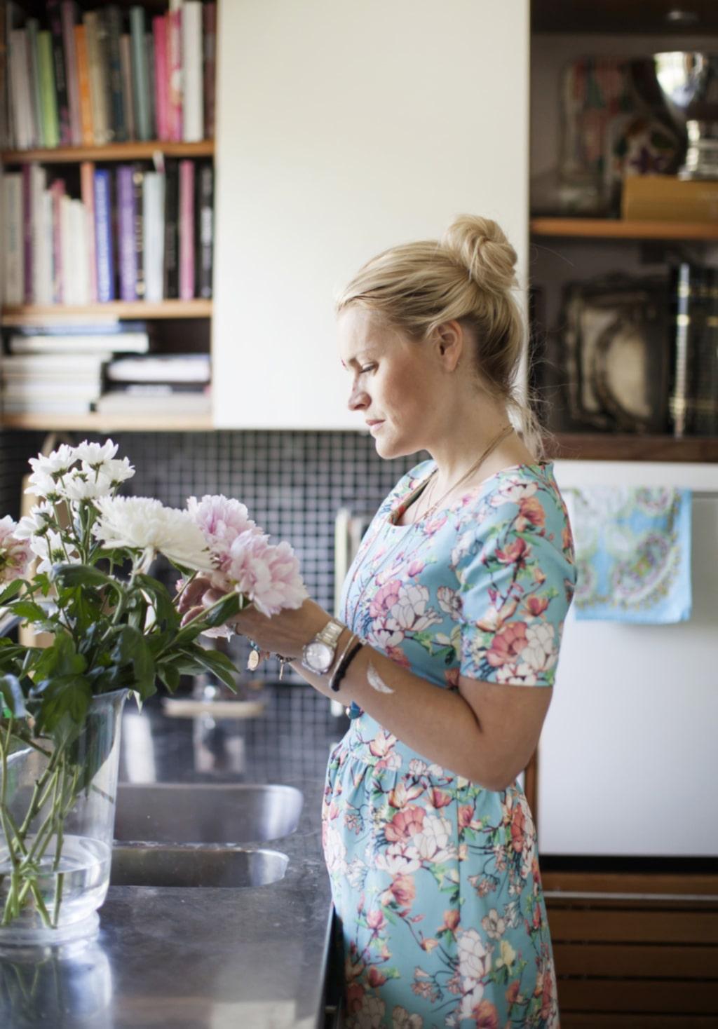 40-talshus. Emilia ordnar blommorna i köket i en vas från Day.