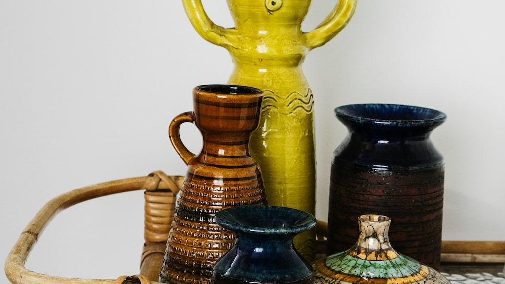 Udda keramik i samling på ett sidobord i rotting och glas. Allt från Vejby loppis.