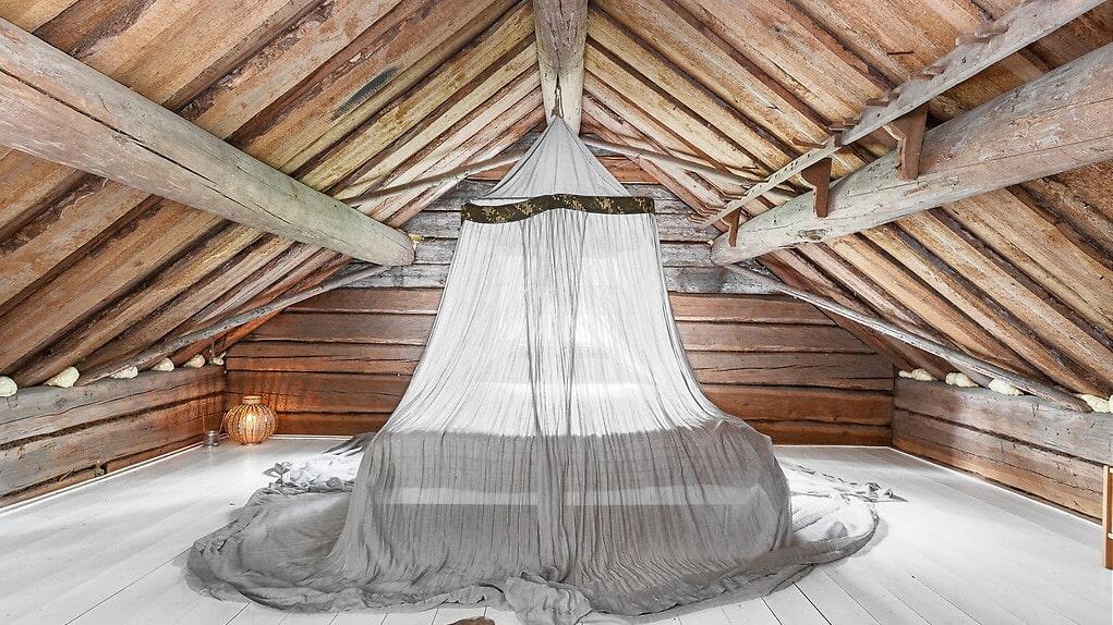 ... som är minimalistiskt inrett med en säng och sänghimmel.