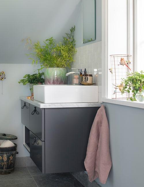 Badrummet är modernt med en platsbyggd kommod med skiva av cararramarmor.