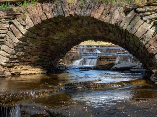 Trappavsatserna i bäckfåran bakom den bågformade bron har naturen själv format i kalkstenen.