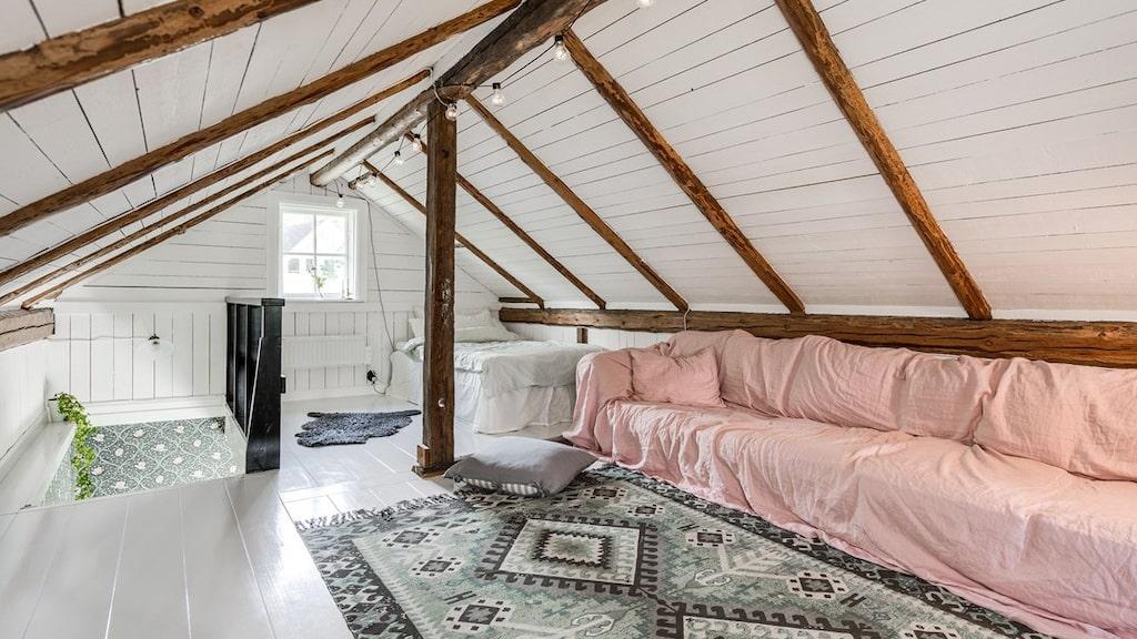 """Rummet från andra hållet. Trappan till vänster och en enkelsäng till höger. Stockar i tak och som """"pelare""""."""