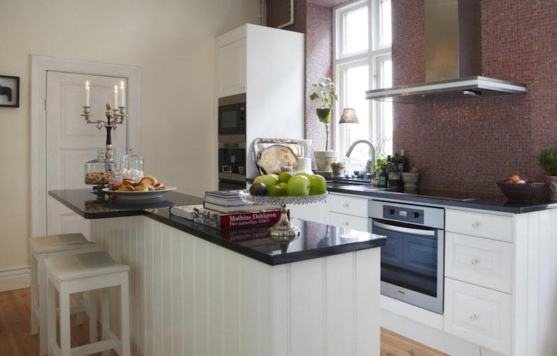Det vita köket från Ballingslöv och har försetts med bänkskivor i svart granit. Vitvaror, Miele.