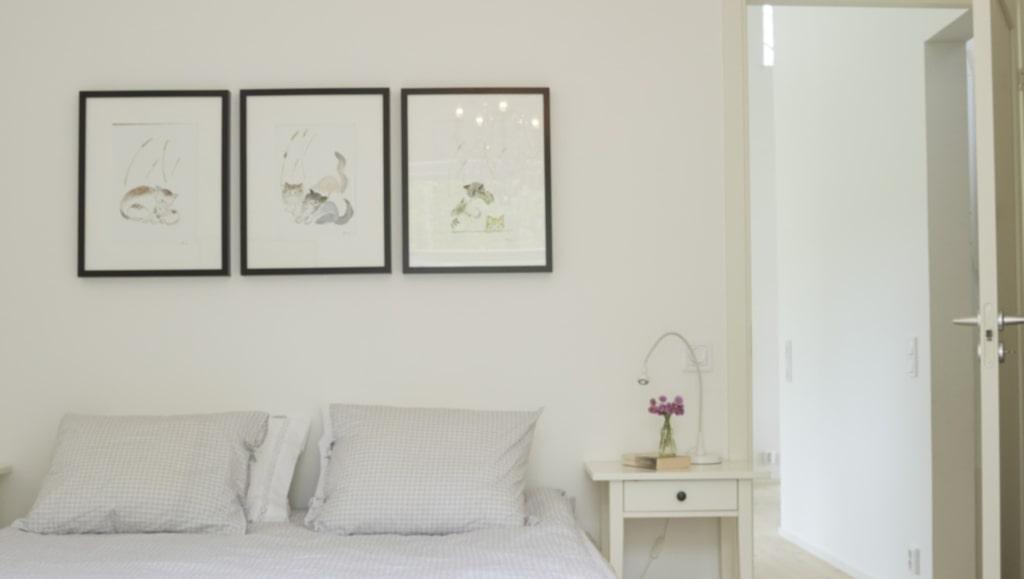 Svalt sovrum för god nattsömn.På väggen hänger tre tavlor som Camillas mamma målat. Påslakan från Åhléns,sängbord, Ikea.