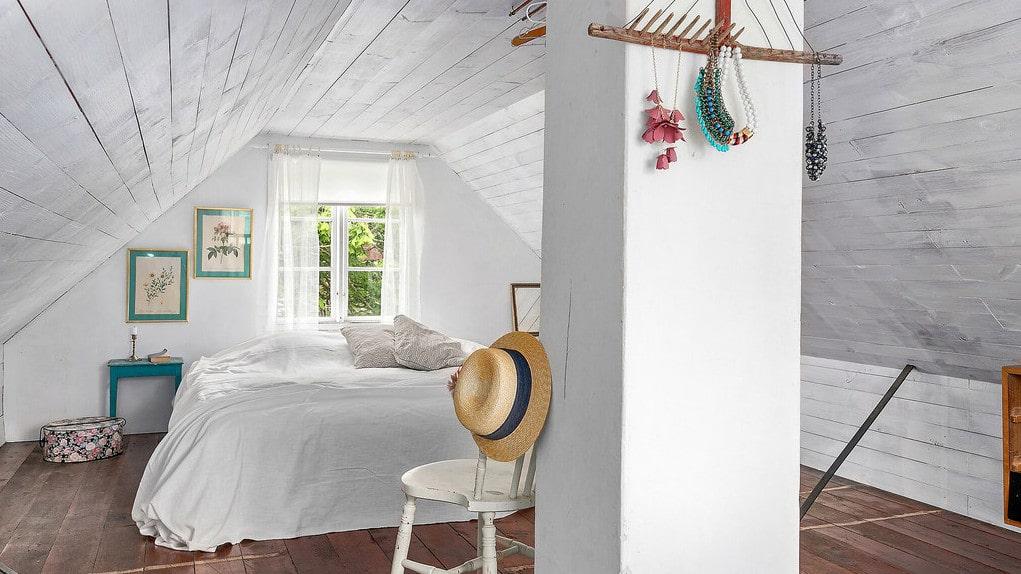 På övre plan finns ett sovrum – med både trägolv och murad skorsten.