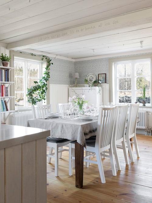 Familjen ville ha ett stort kök med kombinerad matplats och kök. Därför sattes väggen mellan dessa två rum aldrig upp när huset återuppbyggdes. Tapet, Bladmönster Kvist/Blå årtal 1900, Lim & Handtryck.