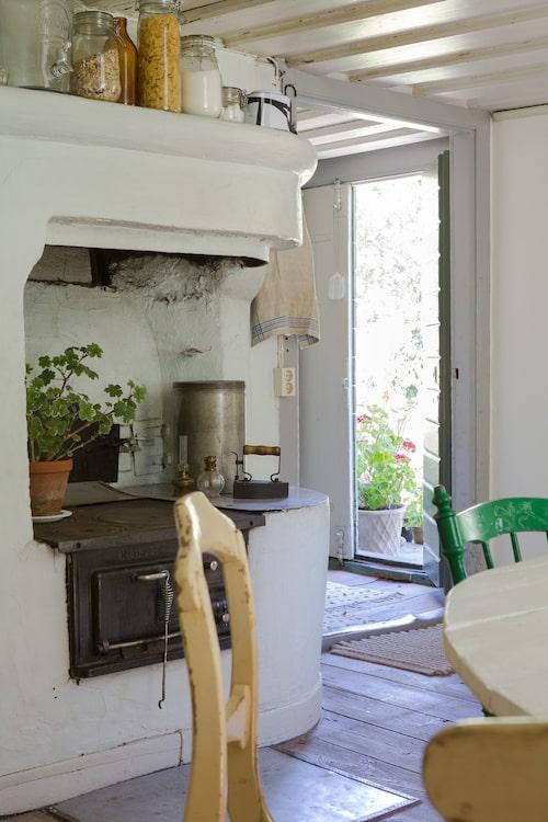Den fina gamla vedspisen och murstocken minner om torpets långa historia. Ärvda och loppisfyndade stolar samsas runt Johans hemsnickrade bord.