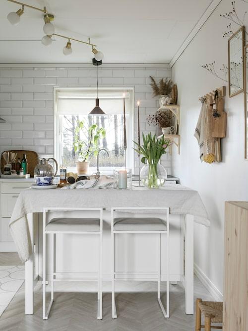 Paret har satt in en flyttbar köksö som används till allt från bakning till frukost- och buffébord. Stol, Bycrea. Laminatgolv med mönster av fiskbensparkett, Tarkett. Fönsterlampa, Ellos.