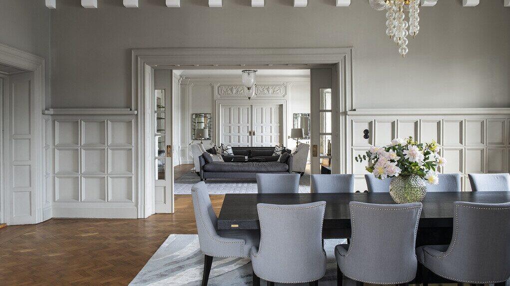 Vy från matsal in till vardagsrum. Notera de vackra väggpanelerna, dörrarna och taket.