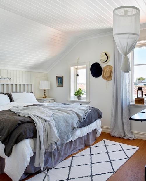 Parets säng står placerad på sju stycken 30 centimeter höga och 60 centimeter djupa köksskåp från Ikea. De har plats för massor av förvaring. Sängbord och säng har Per tillverkat. Sänglampornas fötter är arvegods. Lampskärmar, sängkjol och överkast i linne har Ellinore sytt. Matta, H&M Home.