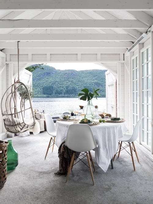 Vid fint väder öppnar Gunn upp båthusets portar för att kunna njuta av den vackra utsikten över sjön och bergen. Hängstolen från Granit, stolar från Cult furniture, bord från Viddals gartneri.