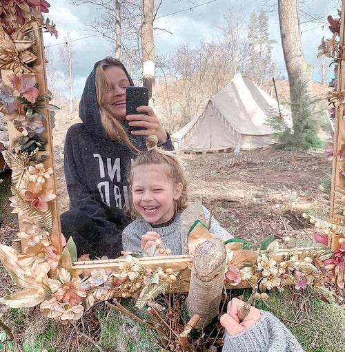 """""""Vår strävan ska fortsätta vara att alltid ge sig själv de bästa förutsättningarna att må så bra som möjligt, leva så 'sant' det går, och följa det som känns rätt – inte fastna i ekorrhjul eller andra destruktiva levnadssätt"""", säger Amalia. Här med ett av barnen. I bakgrunden syns deras glamping-tält som fungerar som vardagsrum."""