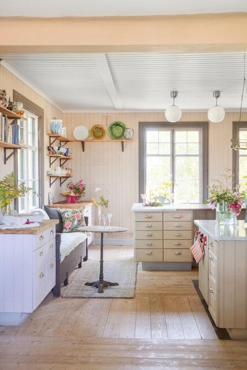 I köket flödar ljuset in. Väggar och tak är målade i en egenblandad äggoljetempera. Hyllorna är fyllda av några av Annettes många loppisfynd.