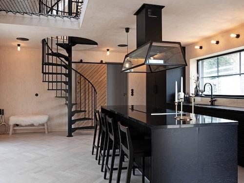 Köket går i svart. Skjutdörren i trä bakom trappan är husets före detta ytterdörr.