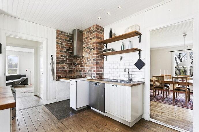 En vacker tegelmur och trä- samt metalldetaljer bryter av den vita färgen som dominerar i köket.