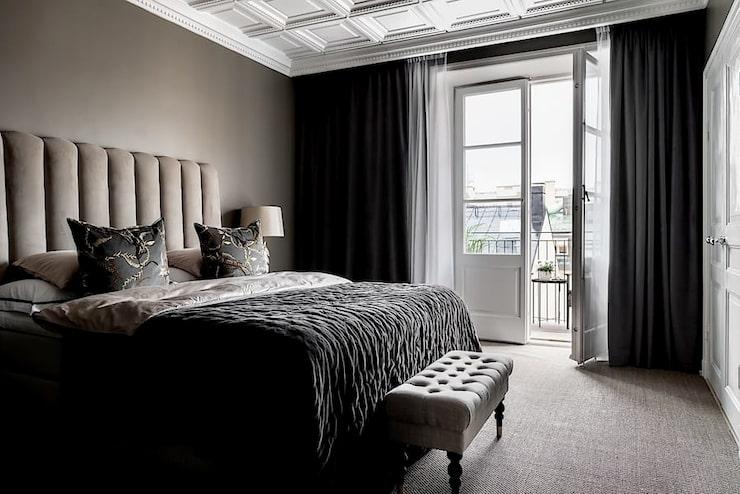 Balkongdörrarna skänker ljus till det stilrena sovrummet.