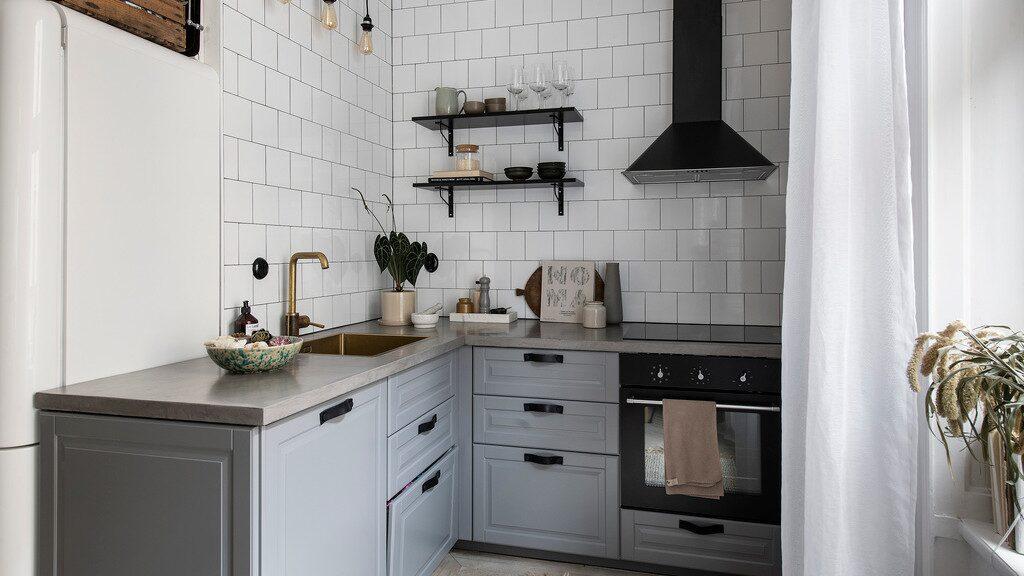 Köket har gråblå luckor och beslag i läder.