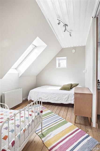 Ett mindre sovrum med charmigt snedtak och takfönster.
