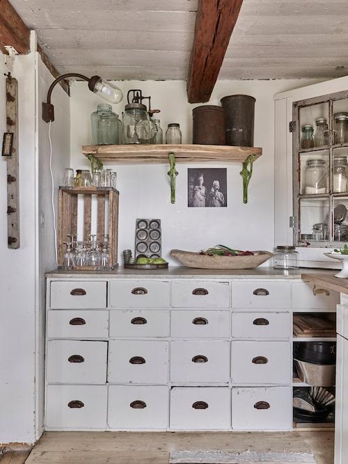 Den antika affärsdisken med marmorskiva fungerar som köksbänk me många praktiska lådor. På hyllan står en gammal charmig visp i glasburk, en föregångare till vår elvisp med skål.