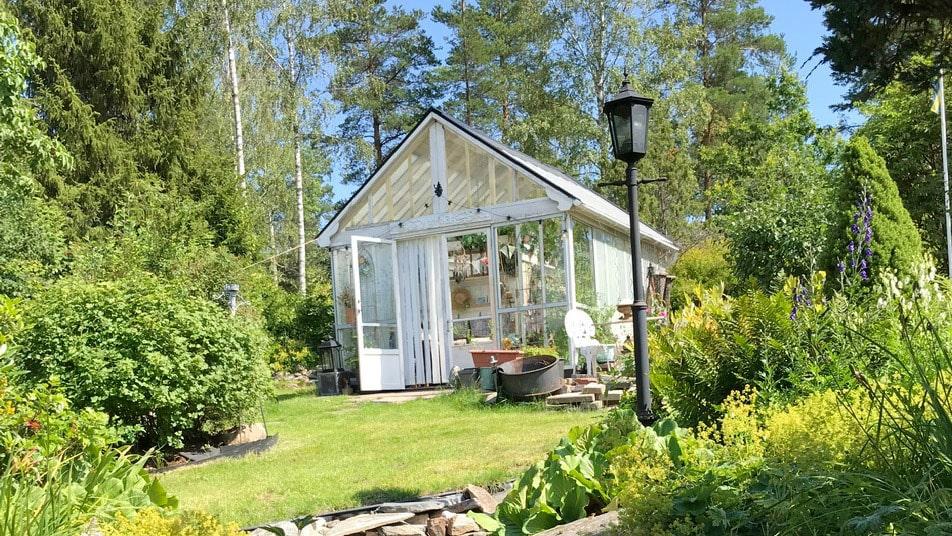 Växthuset på den lummiga tomten är gjort av readörrar för totalt 1000 kronor och material som redan fanns på tomten eller hos Ann Katrins familj.